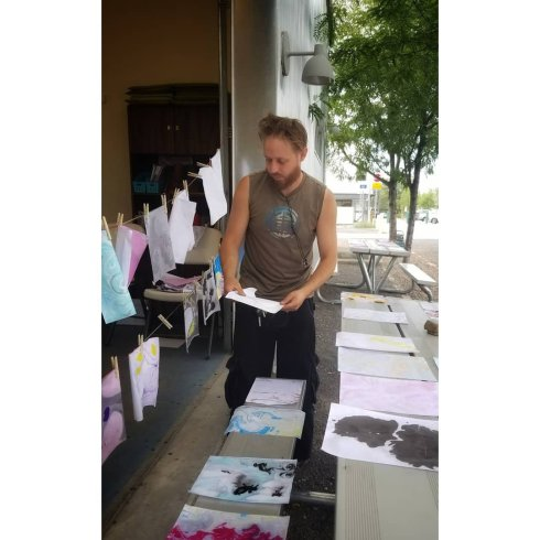 A white man with a beard and sleeveless shirt moves the drying paper from the bench to the clothesline