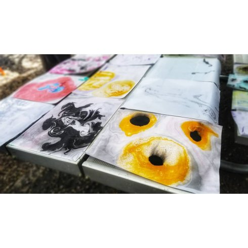 Drying marbled paper on a bench tabletop, striking yellow piece with black eyes