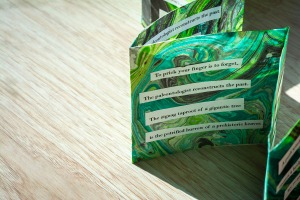 green accordian book, done with suminagashi and collaged poem