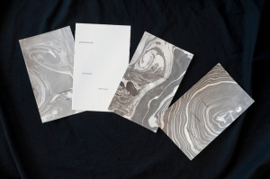 four cards decorated with black ink suminagashi and renga text fanned out on a black background.