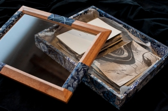 a box with a glass top, collaged with blue origami paper, suminagashi cards and silk inside.