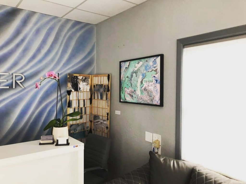 a screen sculpture and suminagashi print in a black frame, light green and pink with blue accents, in the corner of grey matter float spa. a pink orchid sits on the desk.